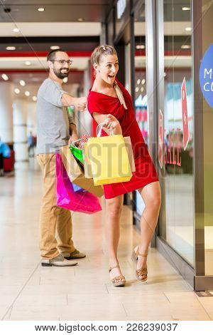 Happy couple at shop window in mall shopping