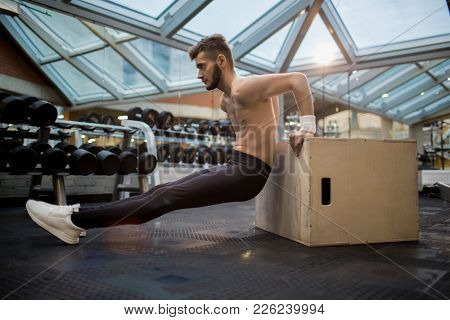 Topless guy in black leggins and white sneakers leaning against jumb-box in gym while exercising