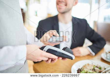 Waitress holding electronic payment machine while client of cafe paying for order by smartphone