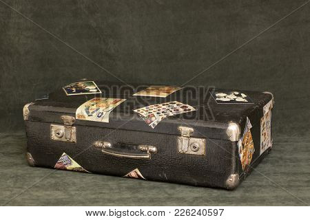 Old Suitcase With Cuffs On A Green Background