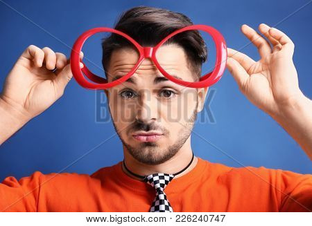 Young man in funny glasses on color background. April fool's day celebration