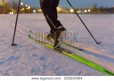 Photo From Back Of Skier With Sticks On Background Of Burning Lights In Winter Day