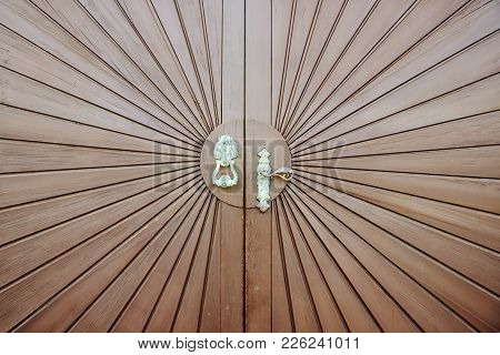 Old Wooden Door With A Copper Handle In The Form Of A Horse Head