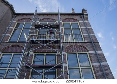 Leiden / The Netherlands - February 7 2018 - A Construction Worker Working On A Old Building Up On T