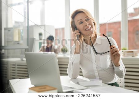 Smiling mid-aged woman in white shirt sitting by workplace and consulting clients by phone