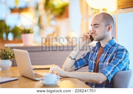 Serious young man sitting in front of laptop, browsing and speaking by smartphone at home office