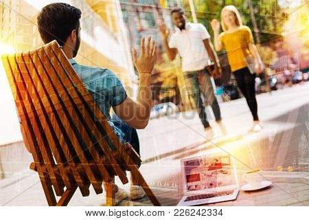 Waving Hands. Calm Young Man Having A Good Time In A Comfortable Armchair Outdoors And Waving To His