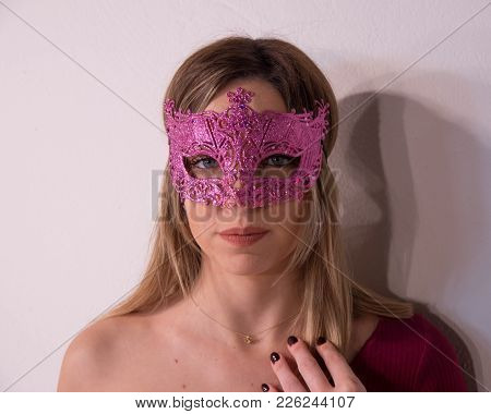 Blonde Girl With Fuchsia Carnival Mask. Masquerade. Portrait Of Beautiful Blond Woman In A Carnival