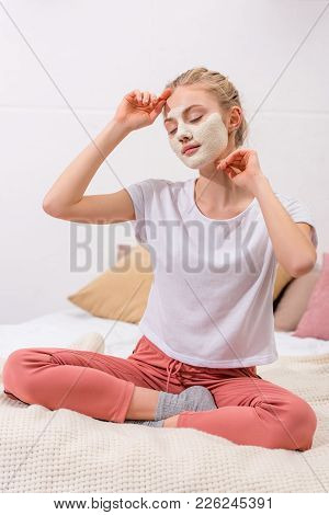 Young Woman With White Clay Facial Mask Sitting On Bed At Home
