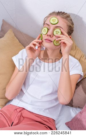 High Angle View Of Young Woman Applying Cucumber Slices On Face At Home