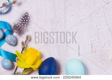 Blue Colored Easter Eggs, Catkins Twigs And Yellow Daffodils Border On White Aged Wooden Tabletop Wi