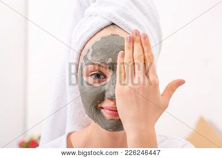 Young Woman With Cosmetic Clay Mask Covering Half Of Face