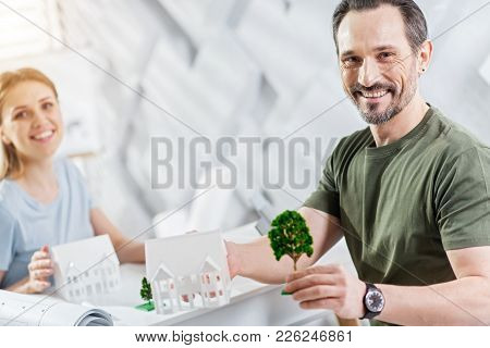 Best Colleague. Good-looking Happy Bearded Man Smiling And Holding A Tree Miniature While Working On