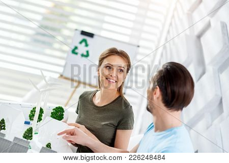 Best Colleague. Beautiful Exuberant Fair-haired Young Woman Smiling And Looking At Her Co-worker Whi