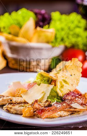 Caesar Salad With Bacon And Chicken On White Plate
