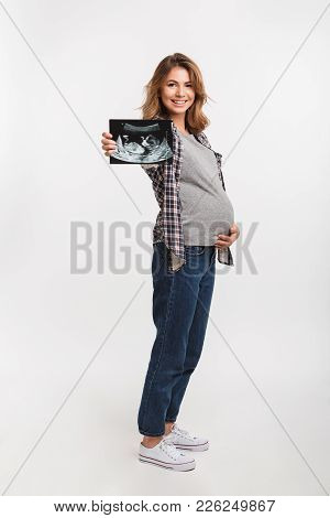 Smiling Pregnant Woman Showing Ultrasound Scan In Hand Isolated On Grey