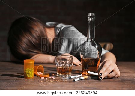 Alcohol, drugs, cigarettes and unconscious woman on background
