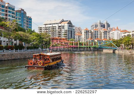 Robertson Quay, Singapore - August 17, 2009: A Traditional Bumboat Motors Up Singapore River Towards