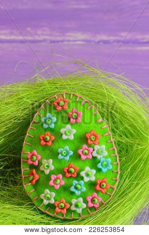 Green Easter Egg Crafts With Colorful Plastic Beads. Felt Egg Crafts In The Nest And On Wooden Backg