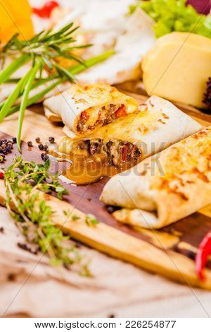 Burritos Filled With Meat And Vegetables On Wooden Cutting Board