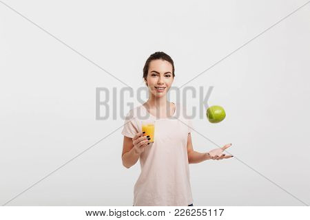 Smiling Beautiful Girl Tossing Up Apple Isolated On White