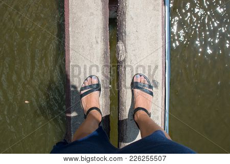 The Tourists Woman Legs Are Crossing Dry Streams With A Bridge Made Of Bamboo Trunks. In The Path Of
