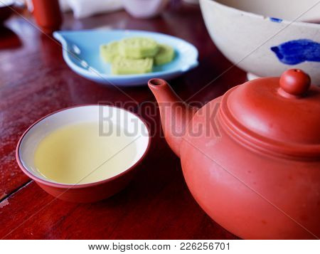 Traditional Chinese Tea Set Compose Of Cup Of Tea, Teapot, And Snack On Wooden Background As Traditi