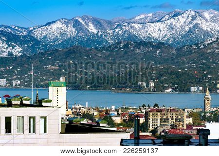 Picturesque View Of The City, The Roofs Of The Houses, The Sea, The Mountains Covered With Snow. Clo