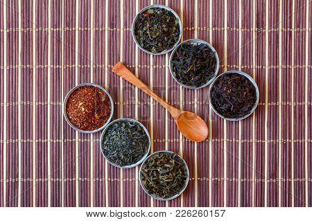 Ivan Tea, Rooibos Marrakech, Black Tea, Green Tea And Wooden Spoon On A Brown Bamboo Mat, Top View C