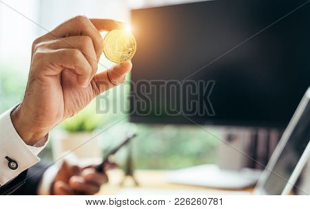 A Busines Man Is Holding A Gold Bitcoin At His Office. He Is Investment In Bitcoin Or Other Cryptocu