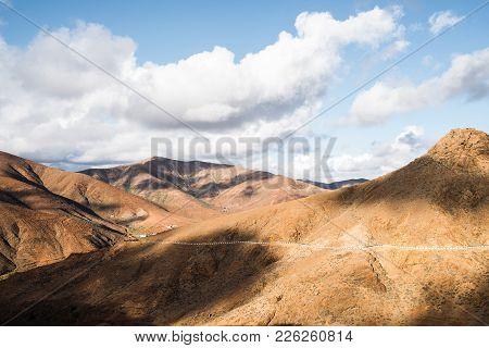 Arid Volcanic Mountain Landscape On Fuerteventura Island Under Partially Clouded Sky