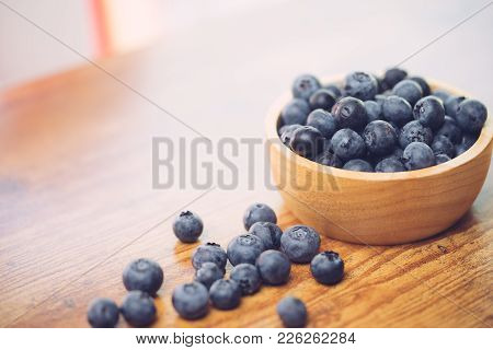 Freshly picked blueberries in wooden bowl.Bilberry on wooden Background. Blueberry antioxidant.Conce
