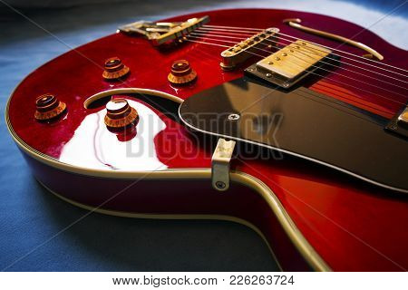Red Acoustic Guitar Close Up In Blue Background