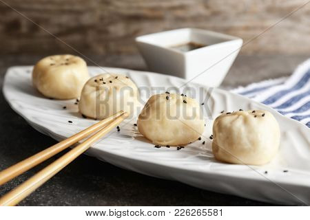 Plate with tasty baozi dumplings on table