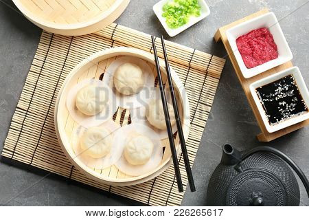Bamboo steamer with tasty baozi dumplings on table
