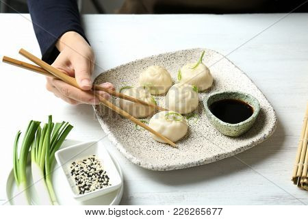Woman eating tasty baozi dumplings at table