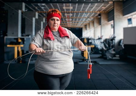 Fat sweaty woman, fitness exercise with rope