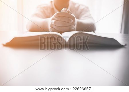 Man Praying On Holy Bible In The Morning.teenager Boy Hand With Bible Praying,hands Folded In Prayer
