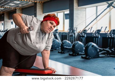 Fat sweaty woman using dumbbells in gym
