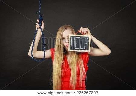 Suicidal Skinny Woman Wearing Elegant Red Dress Holding Help Sign On Dark Board Next To Hanging Rope