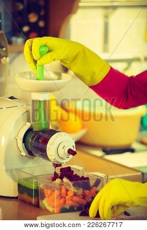 Woman Hands Adding Different Vegetables Red And Green In Juicer Maker. Housewife In Kitchen Making R