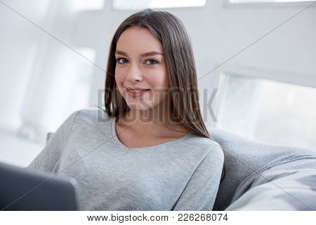 Self-satisfied. Pretty Exuberant Long-haired Slim Girl Smiling And Sitting On The Sofa And Working O