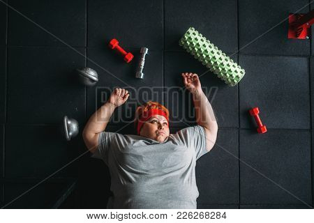 Tired fat woman lies on the floor in gym