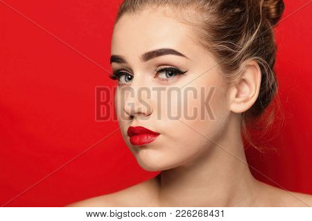 Portrait of young woman with beautiful eyebrows on color background, closeup