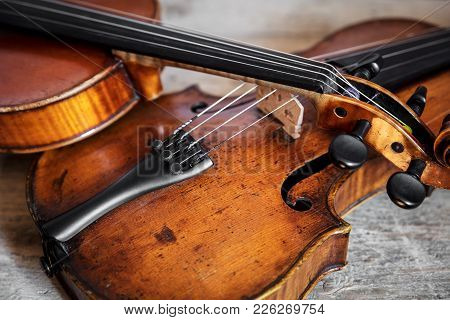 Two Fiddles On A Wooden Background
