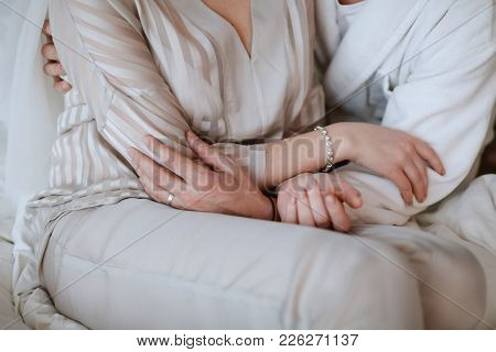 Mom And Her Daughter The Bride Are Sitting, Embracing, Their Hands Are Intertwined