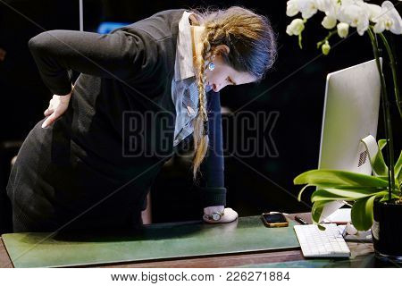 Close-up View Of A Woman-reception Worker Hotel Manager With Pain In Kidneys On Gray Background. You