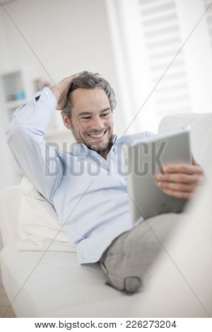 An Attractive Man At Home Using Digital Table