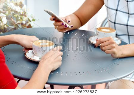 Two Coffee Cups And Hands Of Young Women With Smartphone At Outdoor Cafe