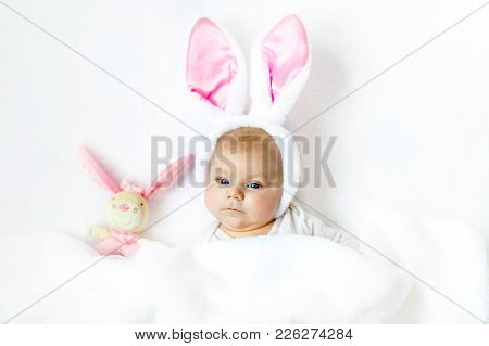 Adorable Cute Newborn Baby Girl In Easter Bunny Costume And Ears. Lovely Child Playing With Plush Ra